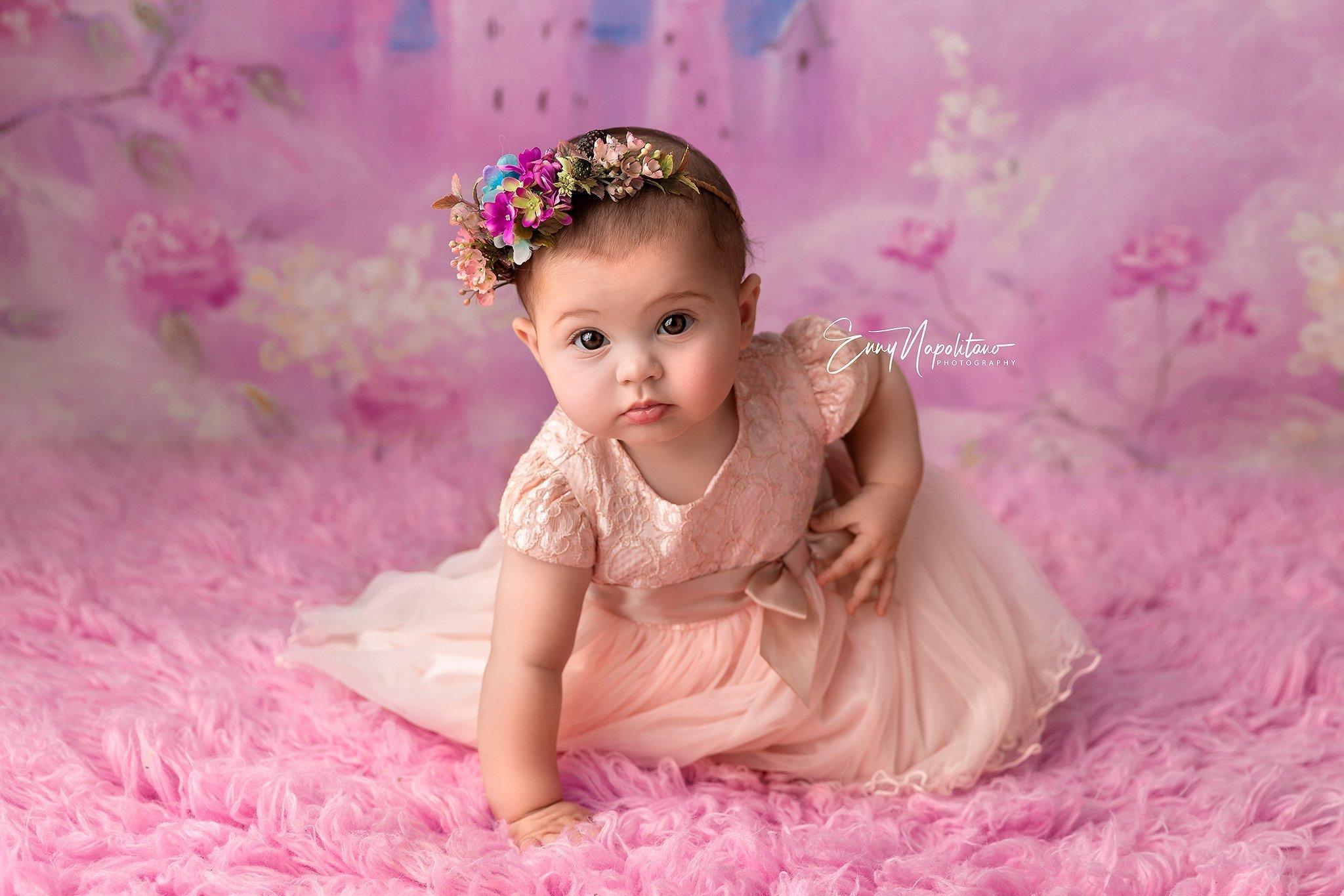 Fotografia di una bambina di 7 mesi mentre gattona in un set fotografico rosa
