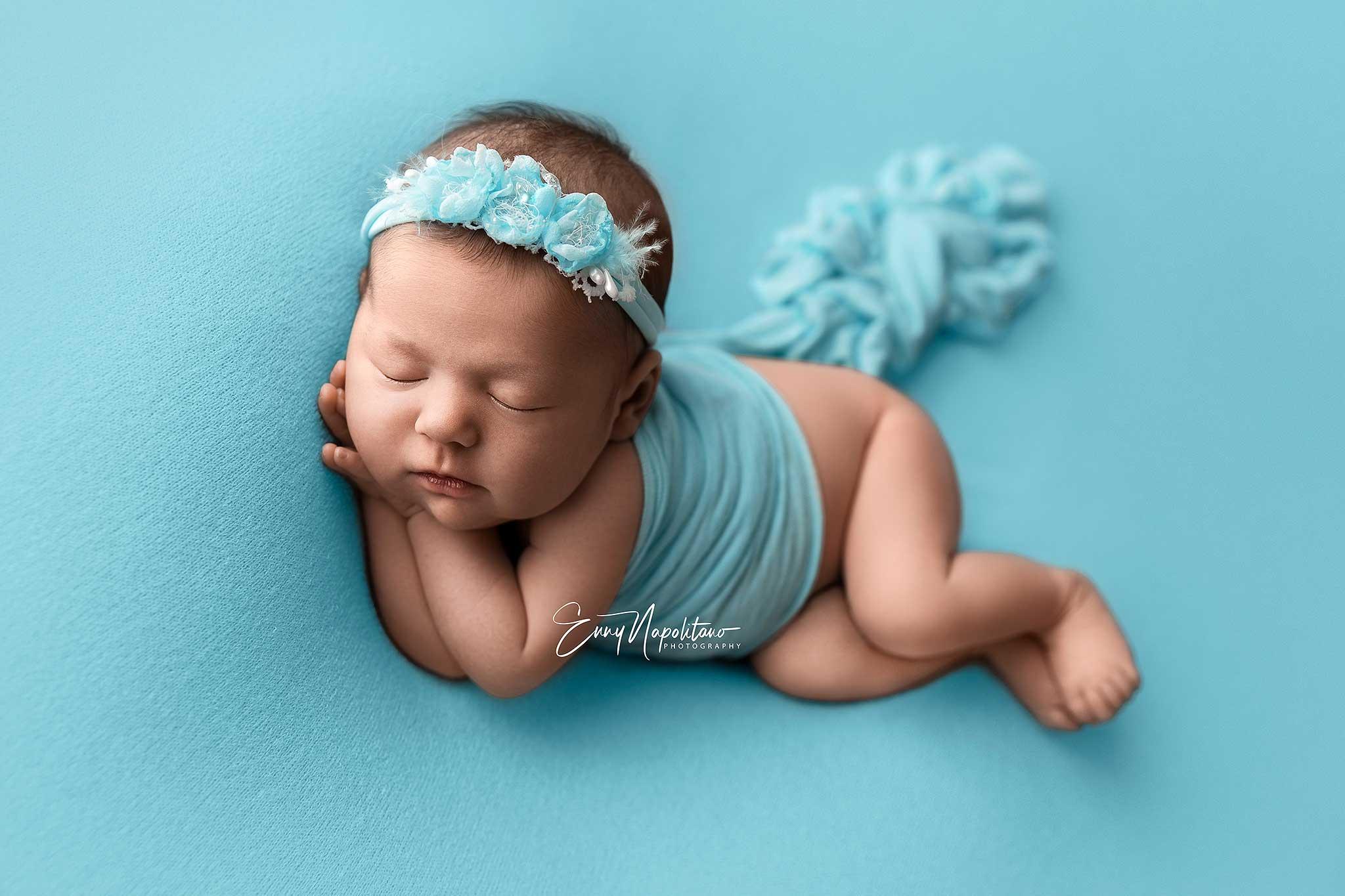 Fotografia di una neonata che dorme in posa di lato (side pose) su una coperta azzurra
