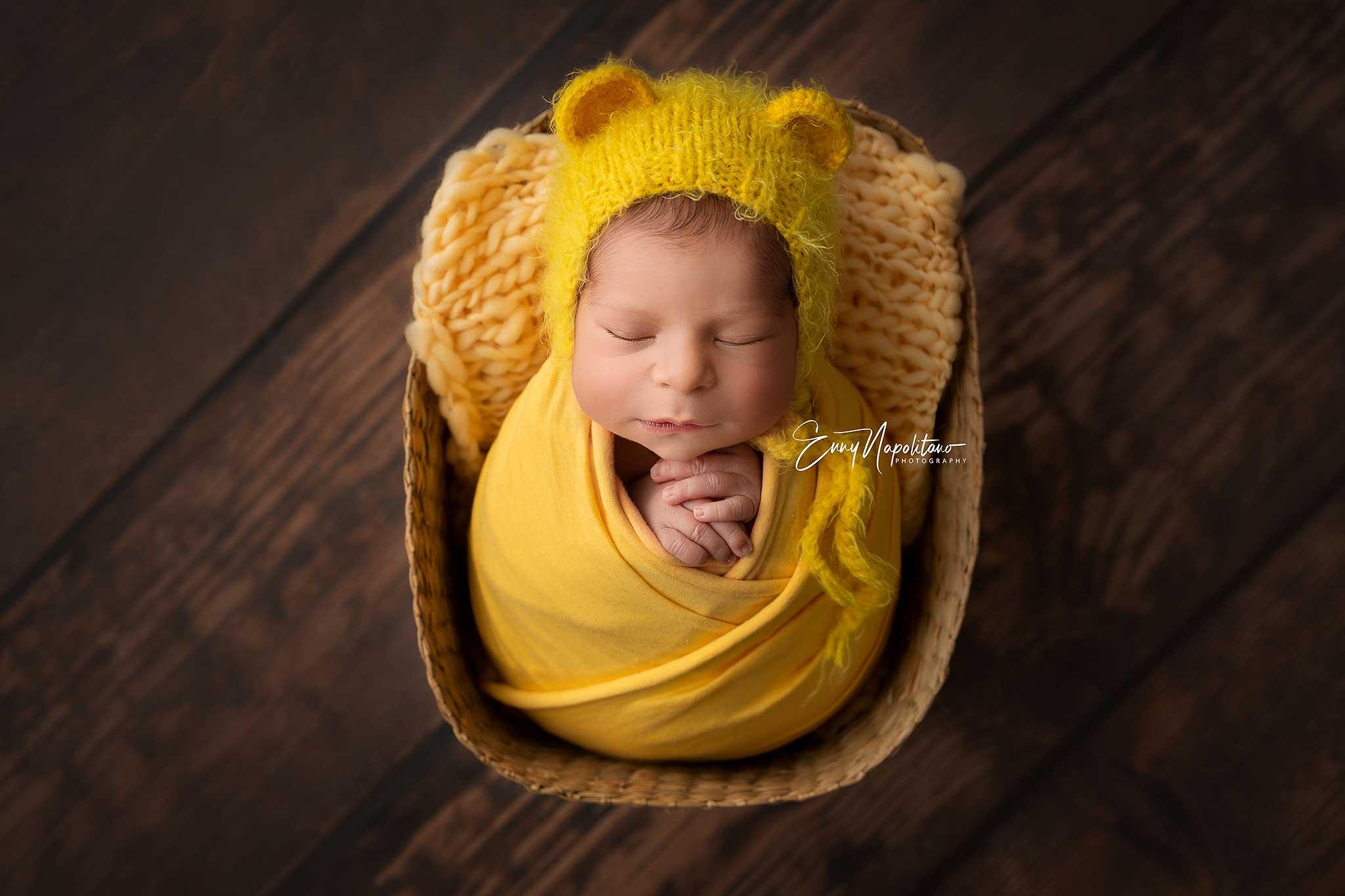 Fotografia di un neonato in un cestino con cappellino da orsacchiotto