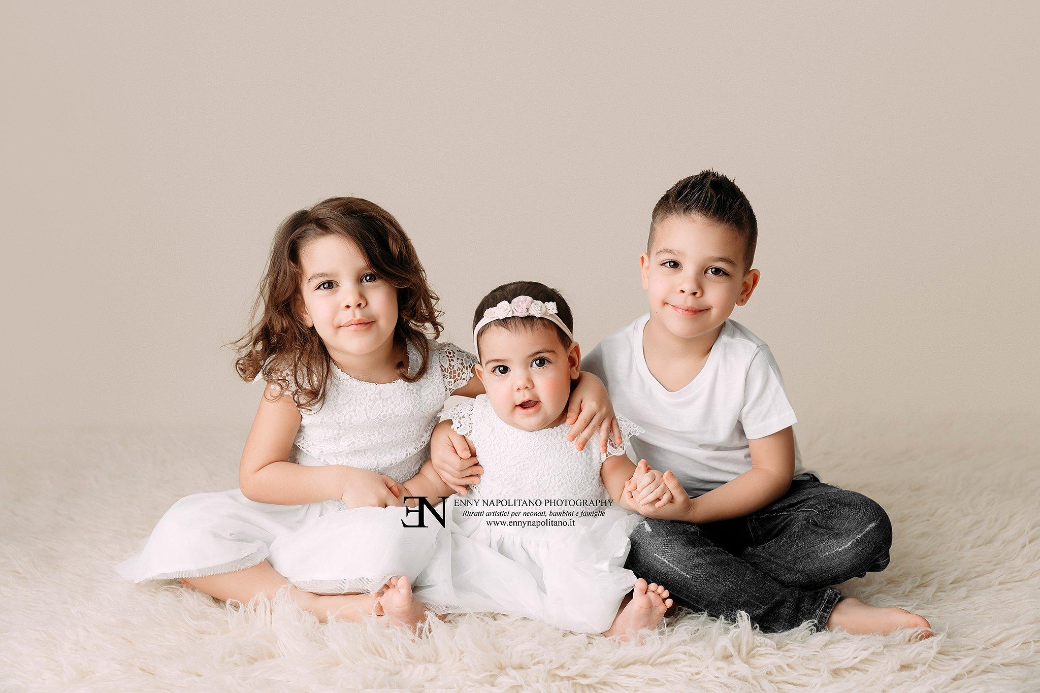 tre fratellini con bimba di 7 mesi durante un servizio fotografico per bebè, bambini e famiglie a Milano