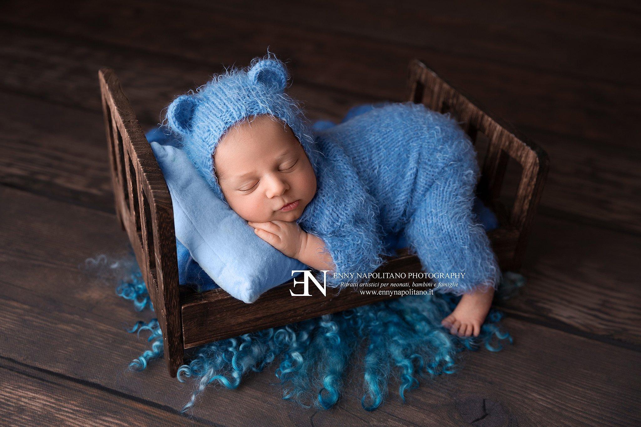 neonato su lettino con orecchie da orsacchiotto e tutina servizio fotografico neonati Milano