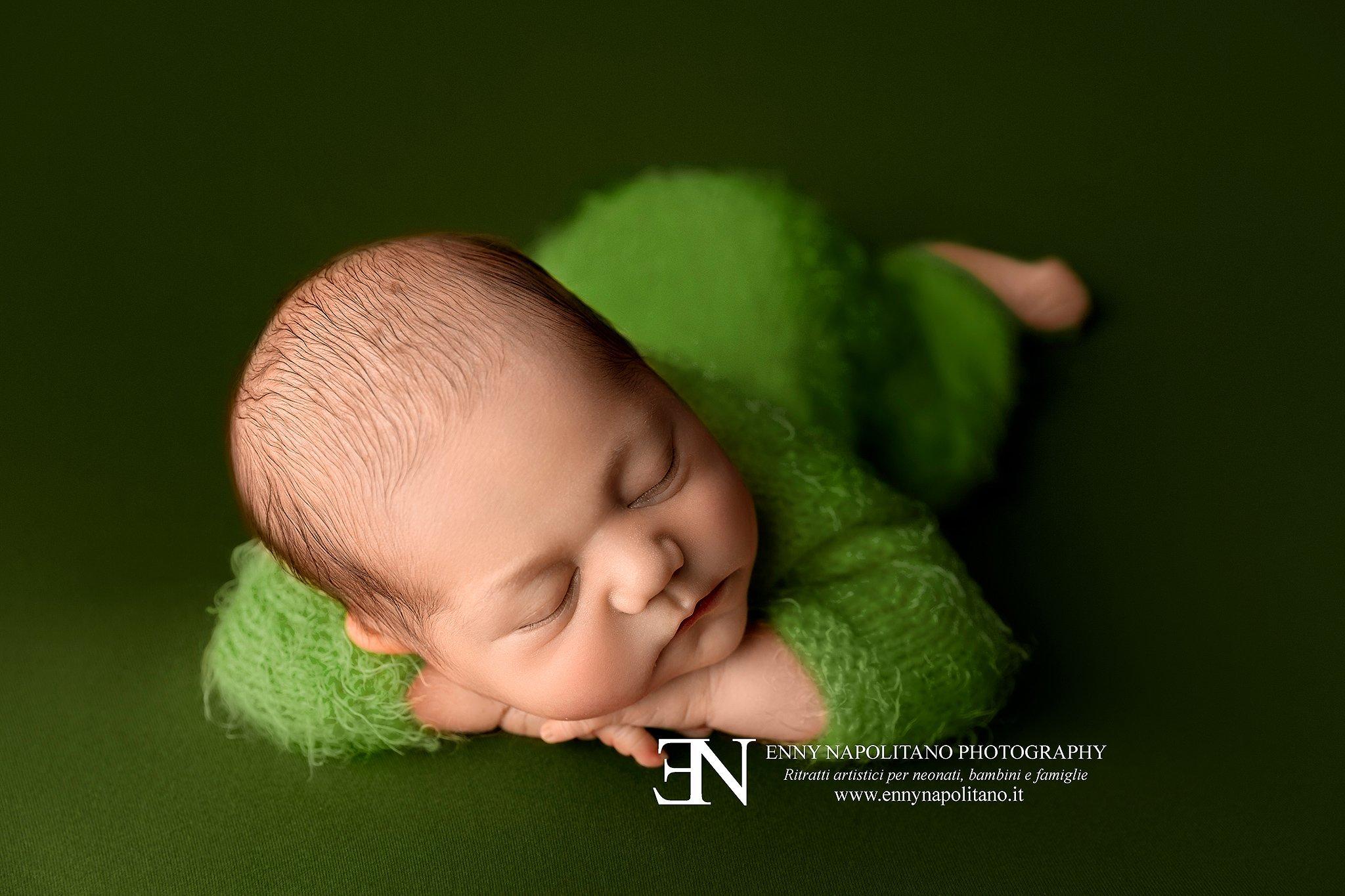 neonato che dorme su coperta verde con tutina servizio fotografico neonati Milano