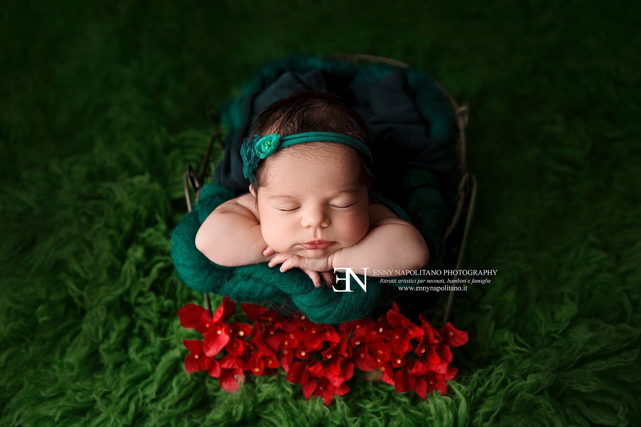 neonata che dorme in un set verde con fiori durante un servizio fotografico newborn per neonati e bambini a Milano