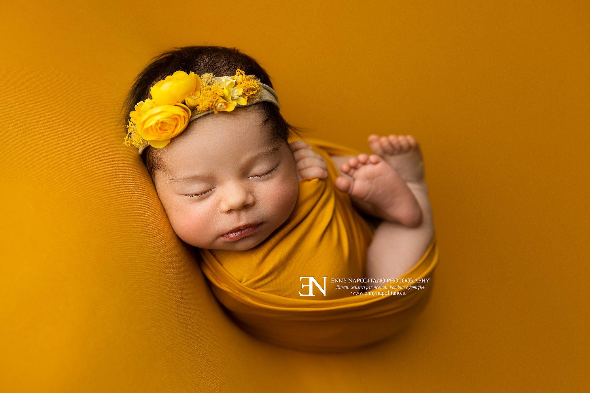 Neonata che dorme fasciata di giallo con fiori durante un servizio fotografico per neonati e bambini Milano