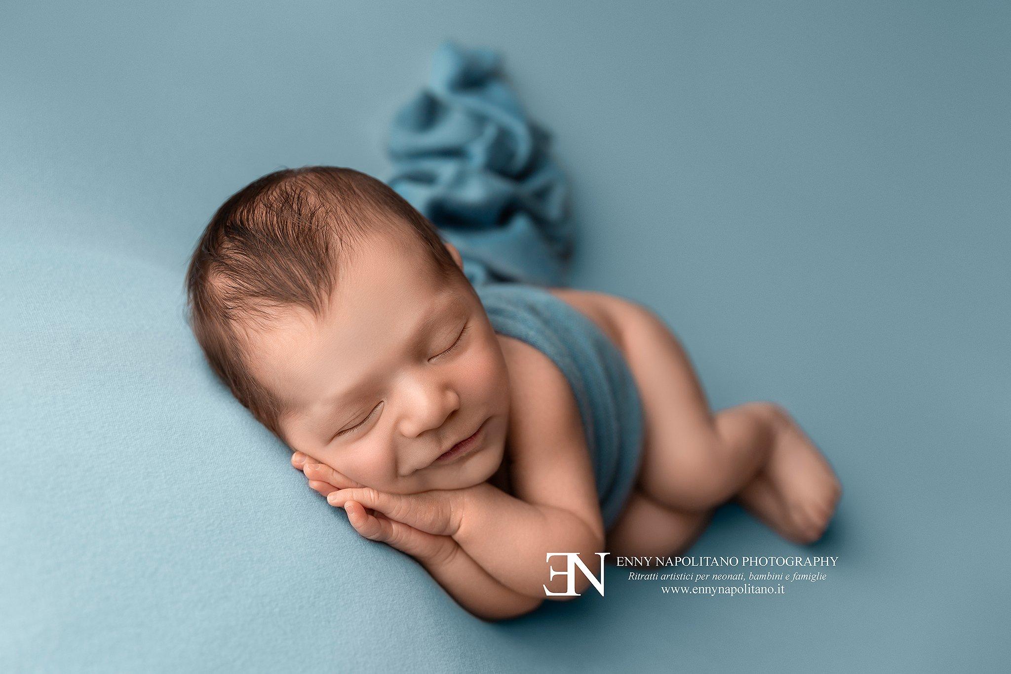 Neonato che sorride mentre dorme durante un servizio fotografico per neonati e bambini Milano