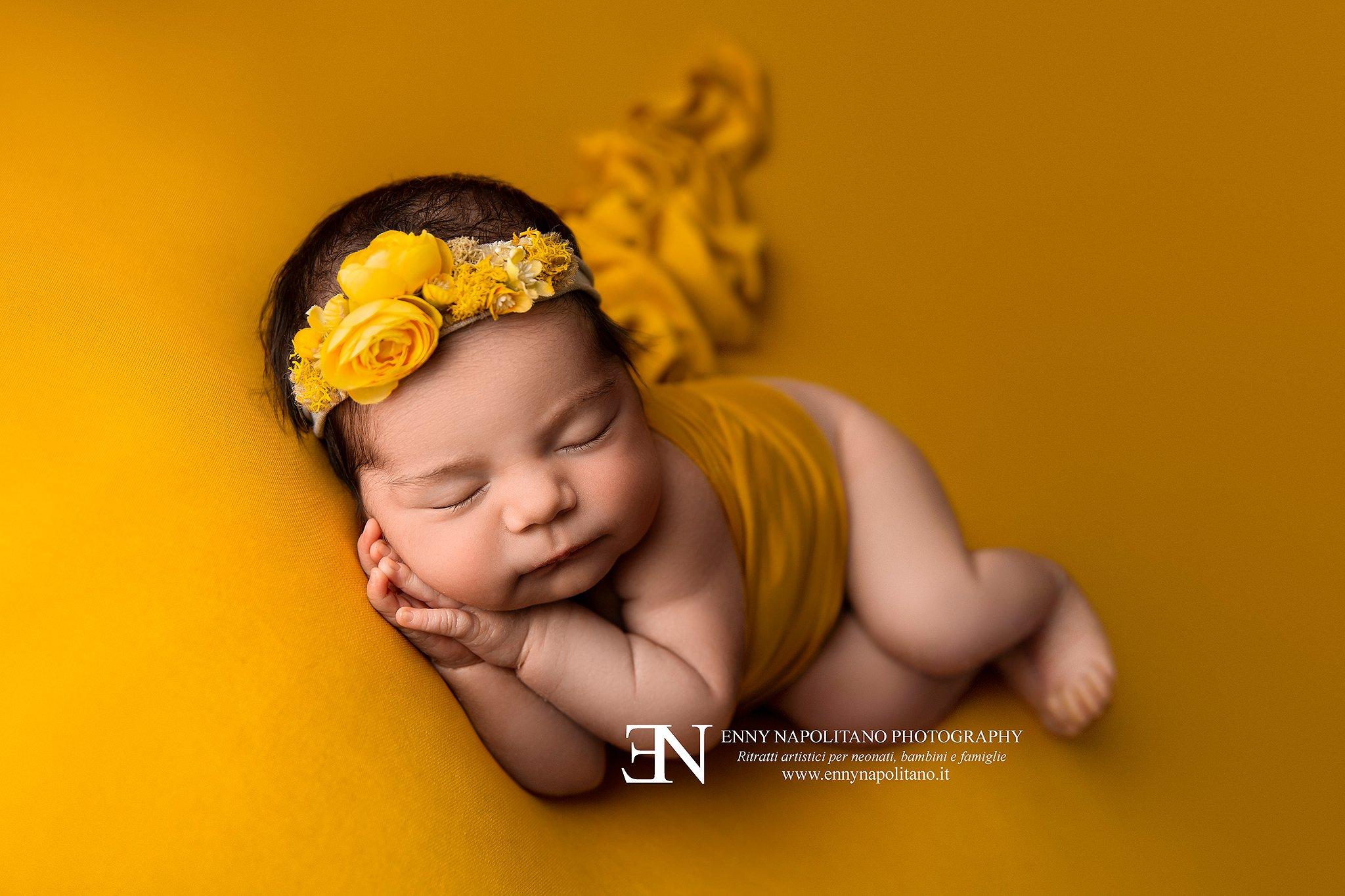 neonata che dorme sul fianco su coperta gialla e arancione durante un servizio fotografico per neonati e bambini a Milano