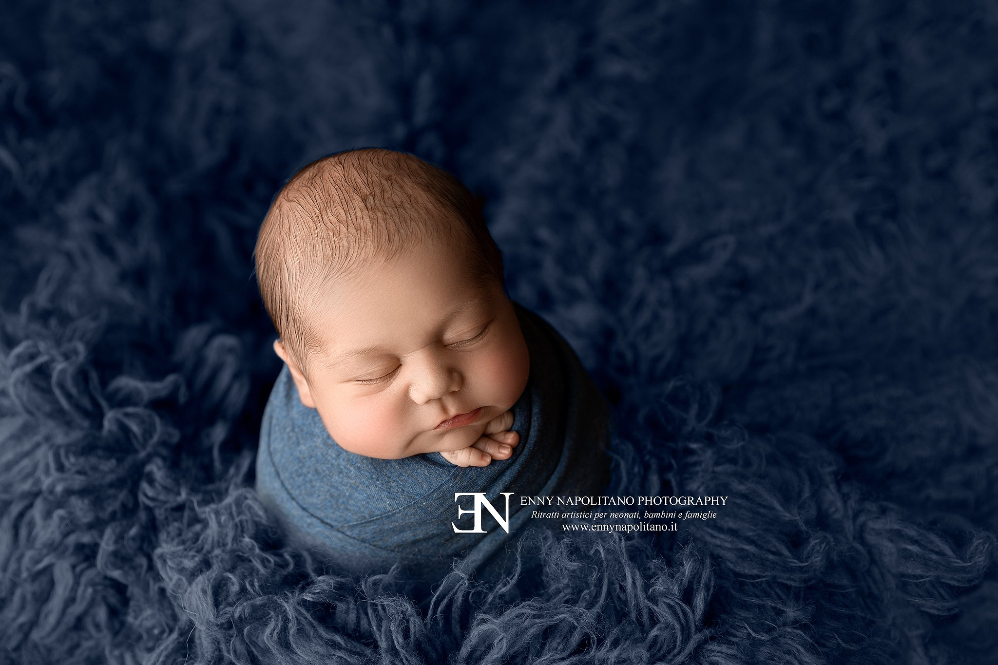 neonato fasciato di blu che dorme durante un servizio fotografico newborn per neonati e bambini a Milano