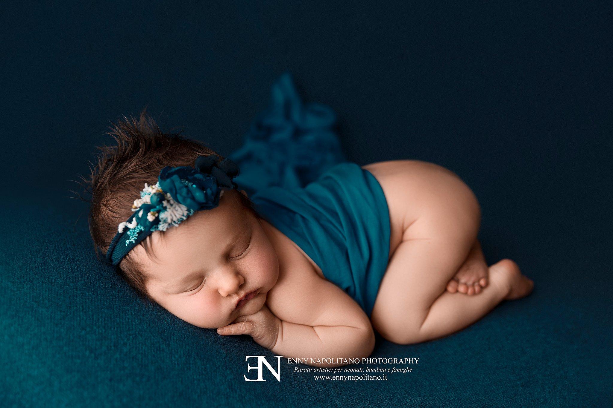 neonata che dorme sulla pancia su una coperta blu petrolio ottanio durante un servizio fotografico newborn per neonati e bambini a Milano
