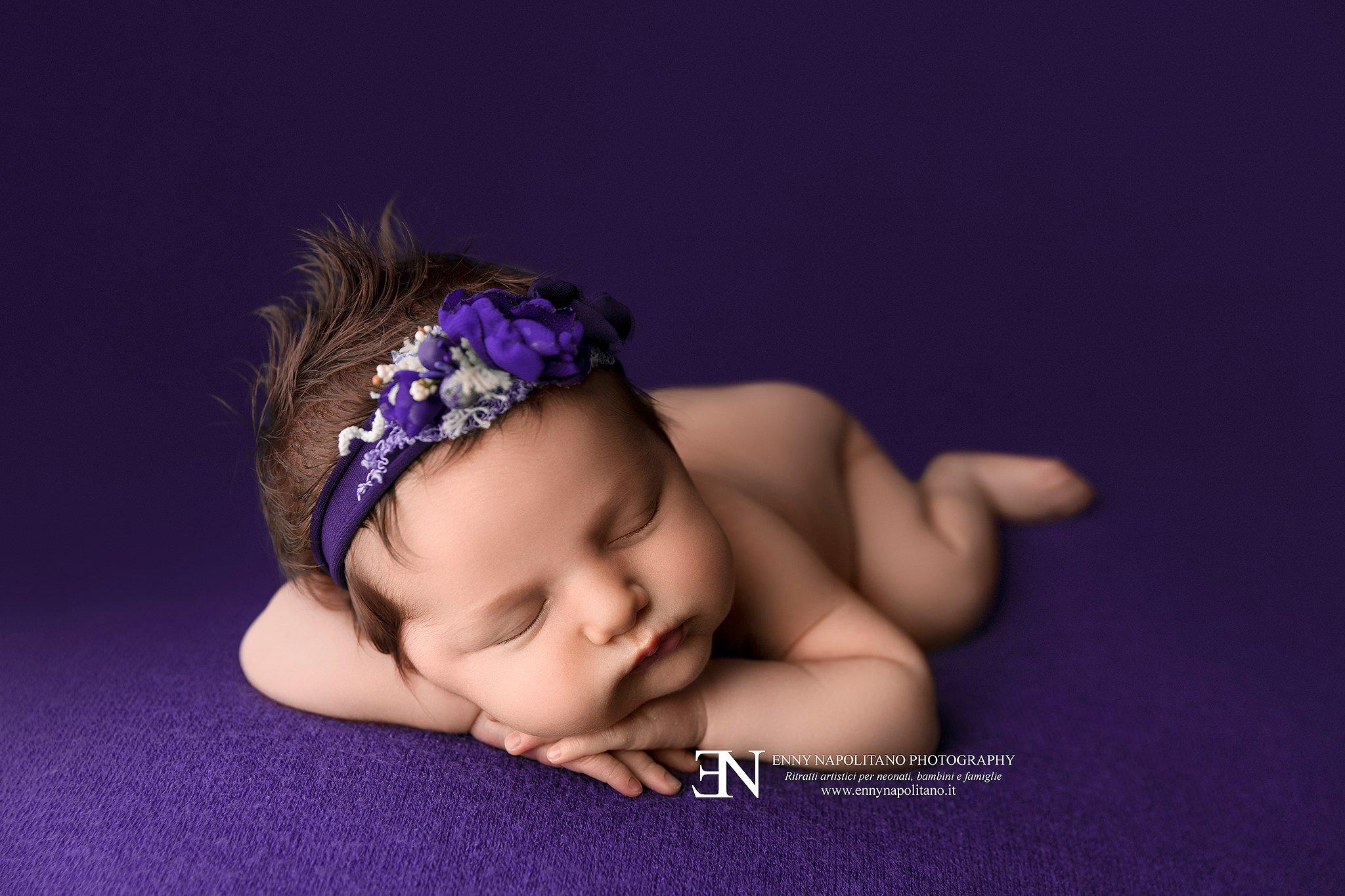neonata che dorme in posa su coperta viola durante un servizio fotografico newborn per neonati e bambini a Milano