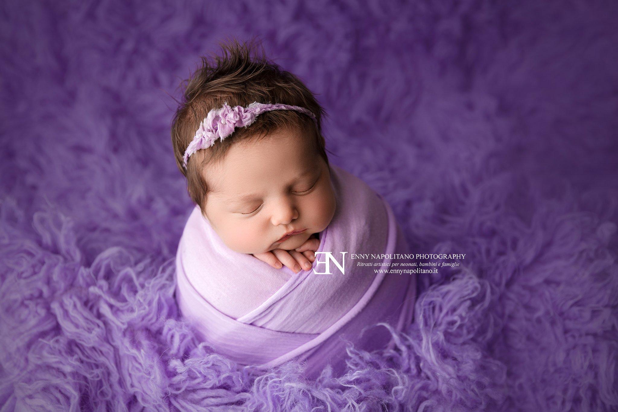 Neonata che dorme fasciata su un tappeto di peli flokati durante un servizio fotografico newborn per neonati e bambini a Milano