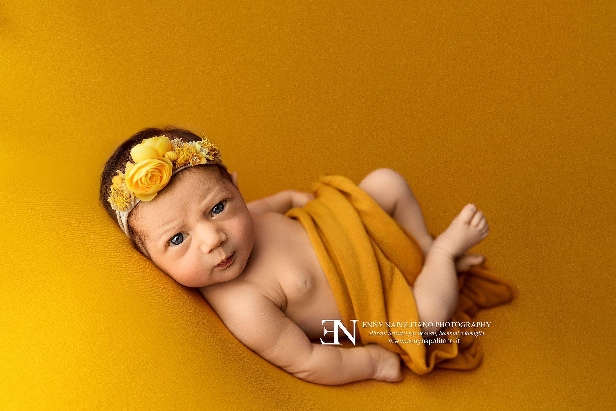 Neonata sveglia che faccia buffa su un fondale giallo e arancione durante un servizio fotografico per neonati e bambini a Milano