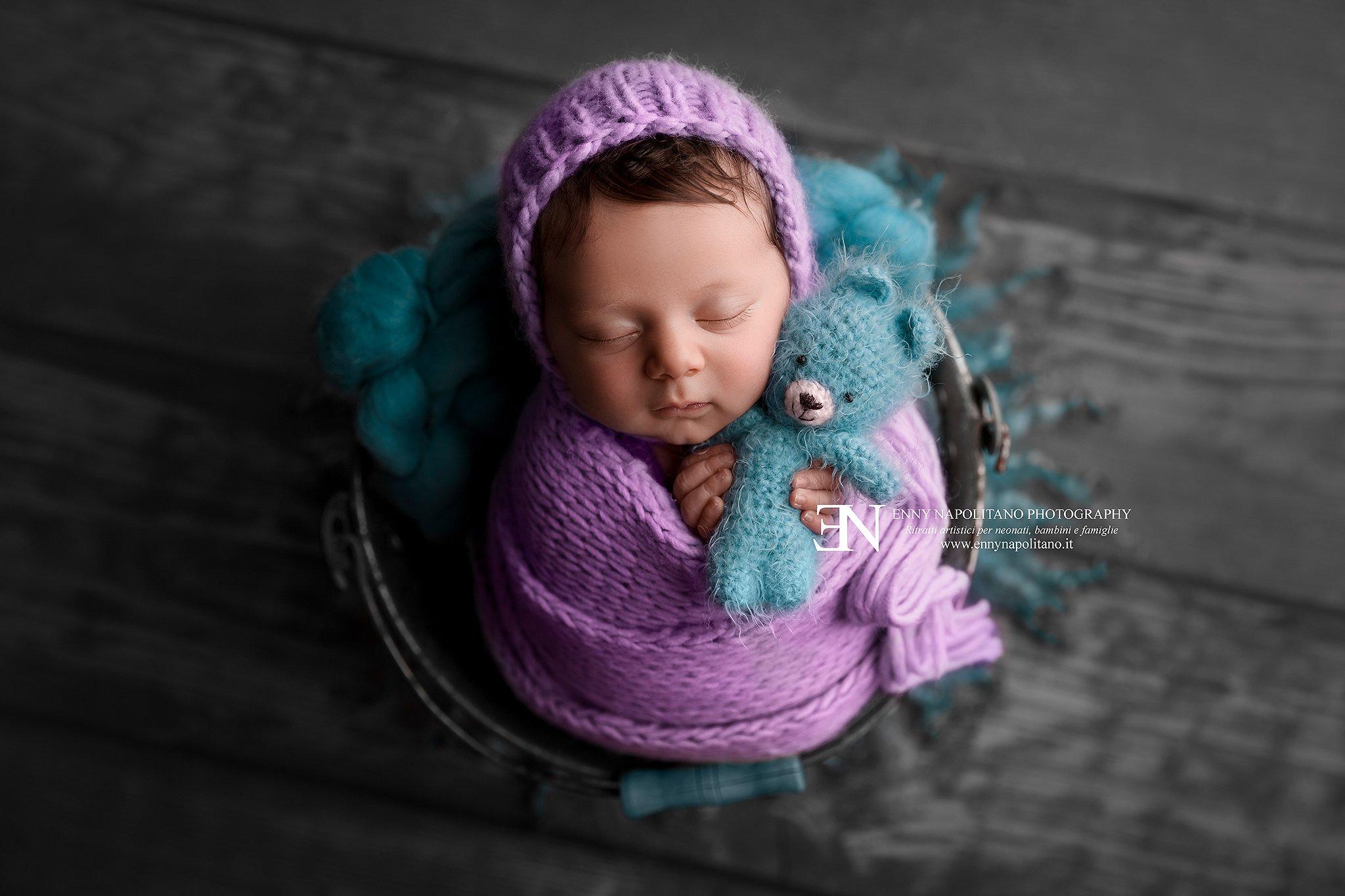 fotografia di una neonata fasciata che dorme in un secchio durante un servizio fotografico newborn per neonati a Milano