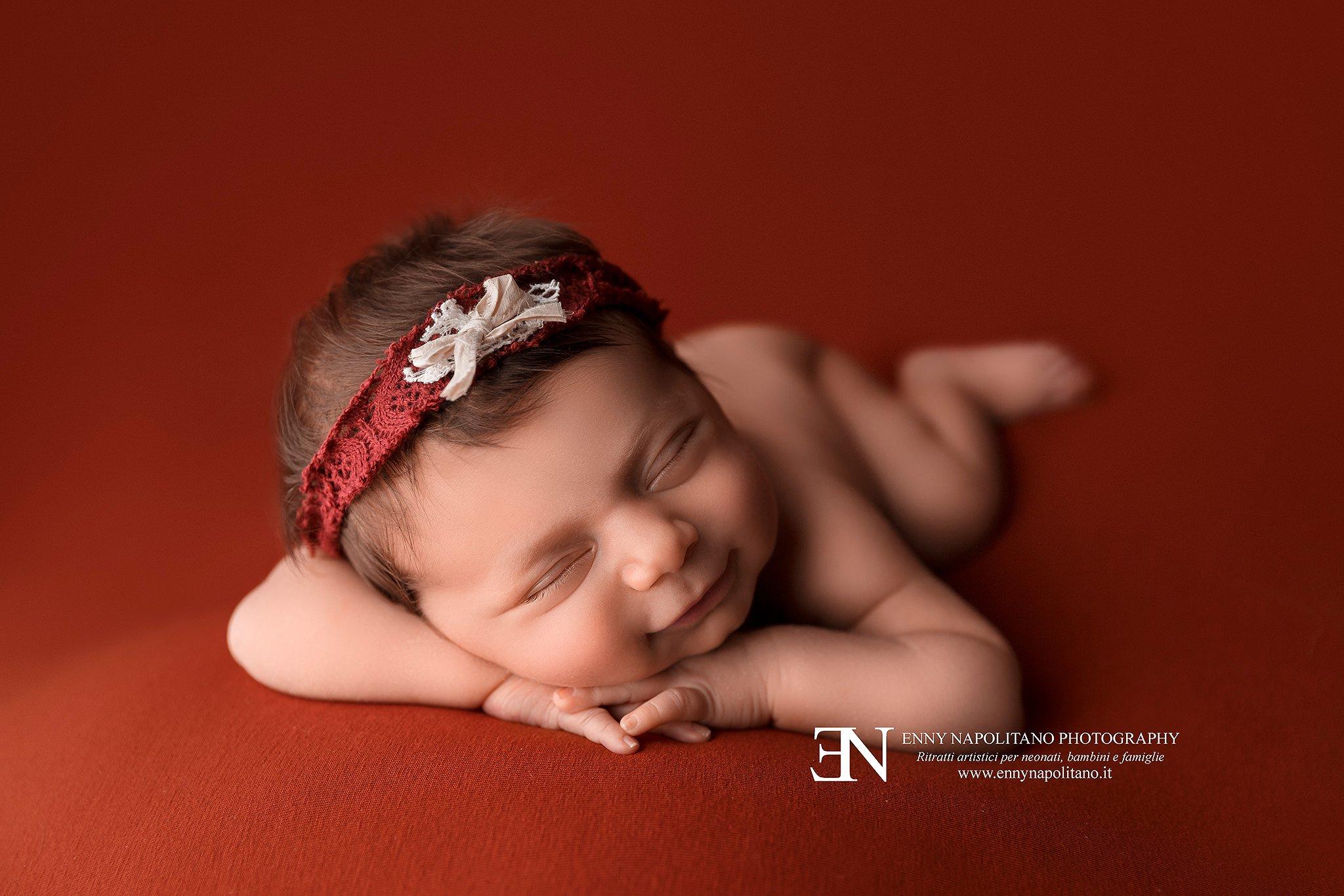 neonata che sorride in posa durante un servizio fotografico newborn a Milano, Pavia, Bergamo, Monza, Brescia, Lodi