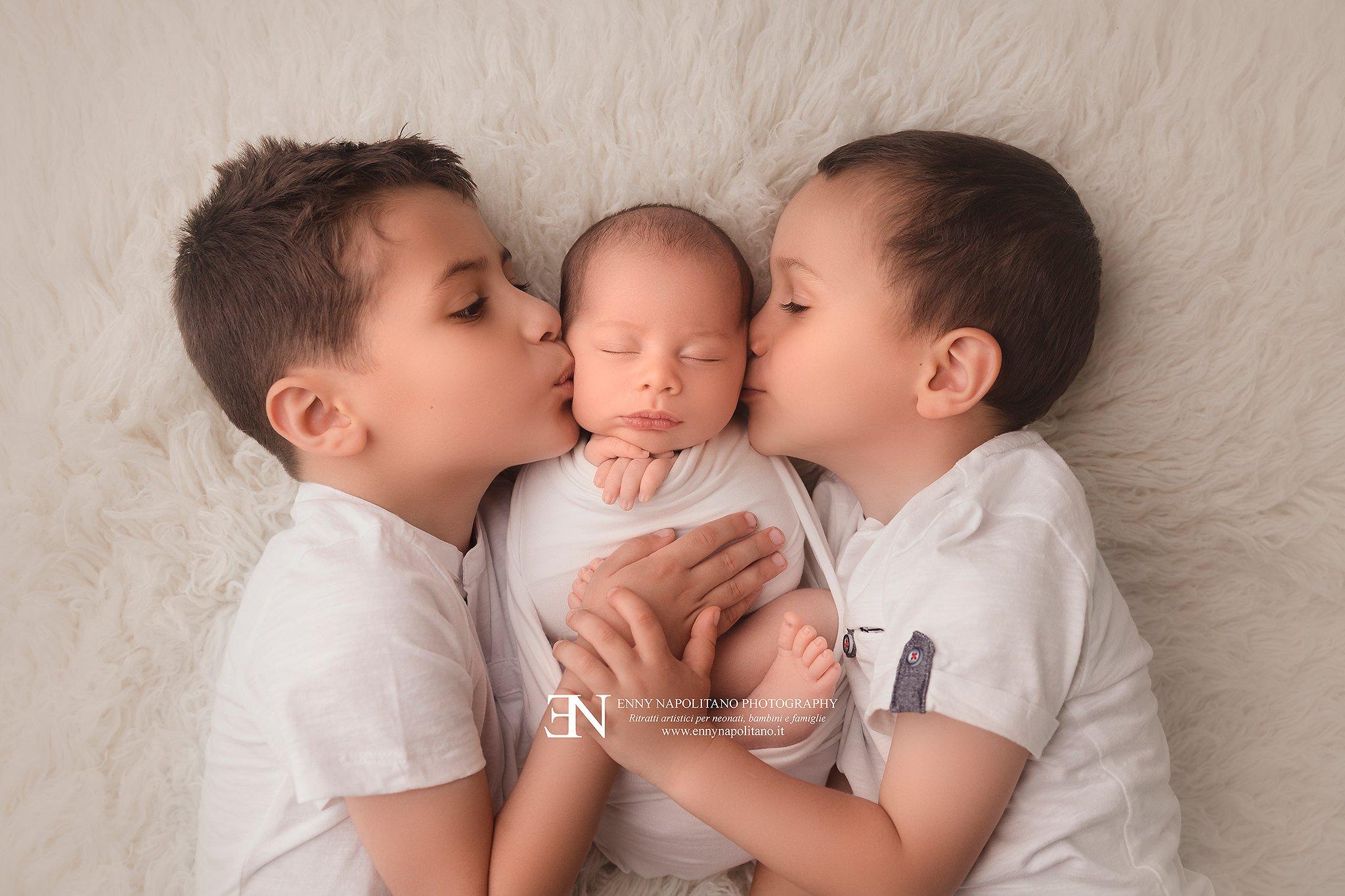 Fratellini che danno bacio al nuovo arrivato
